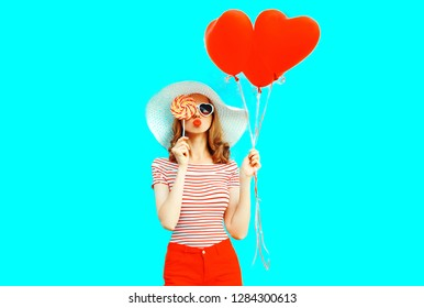 Beautiful young woman with red heart shaped balloons sending sweet air kiss closing her eye with lollipop on colorful blue background