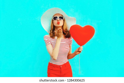 Beautiful young woman with red heart shaped balloons sending sweet air kiss on colorful blue background