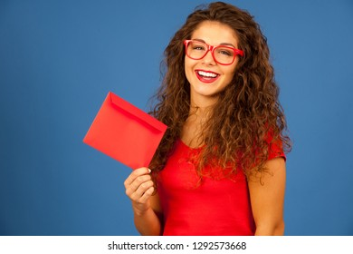 Beautiful young woman in red holding red envelope