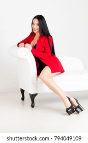 the beautiful young woman in a red jacket on a white sofa