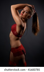 Beautiful young woman in red lingerie and stockings standing in the studio