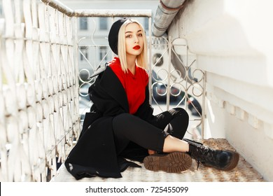 Beautiful young woman with red lips in fashionable black autumn clothes sitting near metal railing