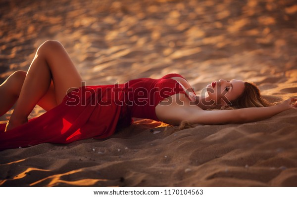 beautiful young woman in red long dress in the sea