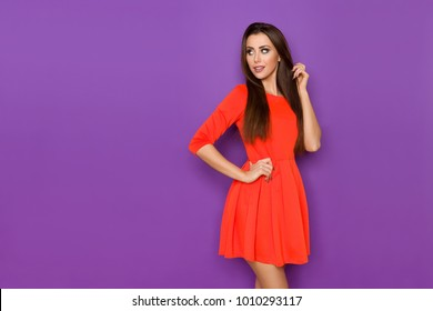 Beautiful young woman in red mini dress is standing with hand on hip and looking away over the shoulder. Three quarter length studio shot on purple background.