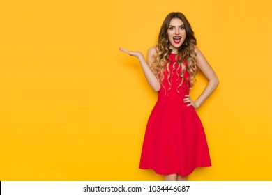 Beautiful young woman in red mini dress is holding hand raised, showing, looking at camera and shouting. Three quarter length studio shot on yellow background.