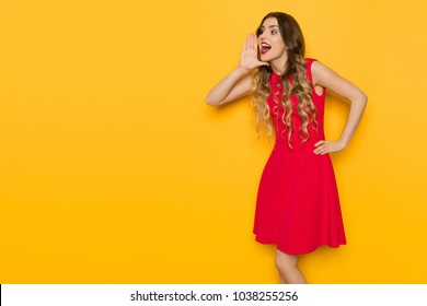 Beautiful young woman in red mini dress is holding hand on chin, looking away and shouting. Three quarter length studio shot on yellow background.