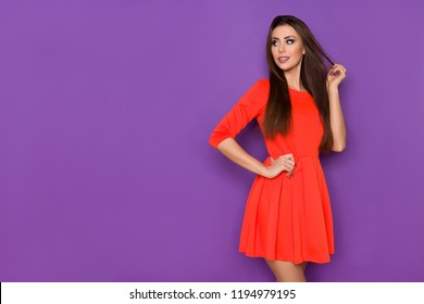 Beautiful young woman in red mini dress is posing with hand on hip and looking away over the shoulder. Three quarter length studio shot on purple background.