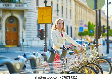 Beautiful young woman in red polka dot dress taking a bicycle for rent in Paris