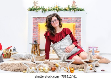 Beautiful young woman in red sitting and holding a pillow. Christmas photo