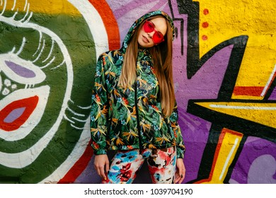 Beautiful young woman in red sunglasses, dressed in hood of bright jacket and colorful pants, with long hair, posing against graffiti wall. Fashion look.