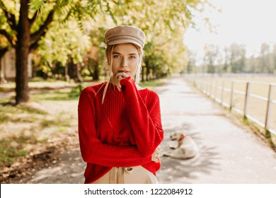 Beautiful young woman in red sweater and nice trendy hat looking thoughtful in autumn park. Attractive blonde in stylish clothes posing outdoor.