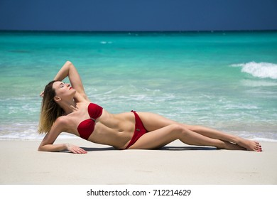 Beautiful young woman in red swimsuit poses on tropical sand of Caribbean sea shoreline at sunny summer day