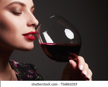 Beautiful young woman with red wine.beauty girl with wineglass. she enjoys the scent of wine