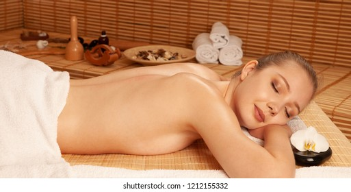 beautiful young Woman relax on massage table in spa salon .
