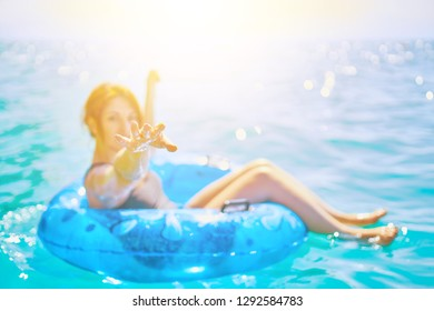 Beautiful young woman relax on inflatable ring in sea water reaching into the camera under the sun