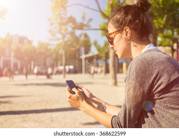 Beautiful young woman relax in Vondelpark Amsterdam smartphone in hands , enjoying the internet outside
