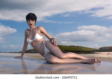 A beautiful young woman relaxes on the beach