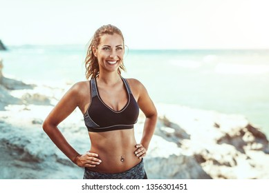 Beautiful young woman relaxing after training on the beach and looking away.