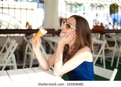 Beautiful young woman relaxing in a bar in the open air, with ice cream. A sunny day in summer.