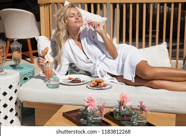 Beautiful young woman relaxing in bathrobe on a hot sunny day and eating her breakfast. Summer vocation. Horizontal.