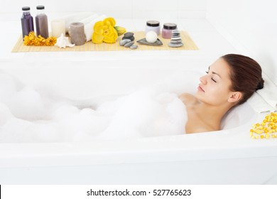 Beautiful young woman relaxing in bathtub with her eyes closed.