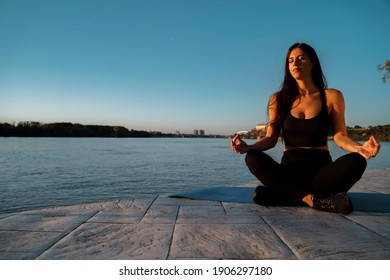 Beautiful young woman relaxing by the river in sunset and meditating, soaking in the sun