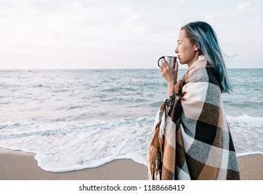 Beautiful young woman relaxing with cup of drink on sand coast near the sea, beach vacations.