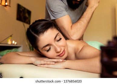 Beautiful young woman relaxing during full body massage at spa.