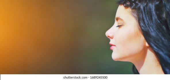 Beautiful young woman relaxing and enjoying sun at sunset. Beauty sunshine girl side profile portrait. Pretty happy woman enjoying summer outdoors. Positive emotion life success mind peace concept.