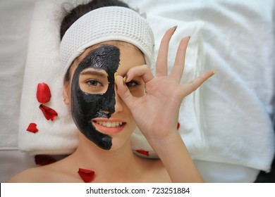Beautiful young woman relaxing with face mask at beauty spa. Happy joyful woman applying black mask on face