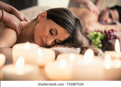 Beautiful young woman relaxing with her partner during traditional Thai massage at luxury spa and wellness center