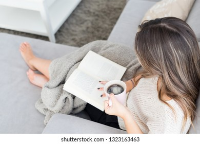Beautiful young woman relaxing at home reading a book
