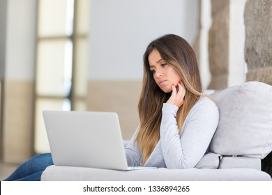 Beautiful young woman relaxing at home on her laptop computer