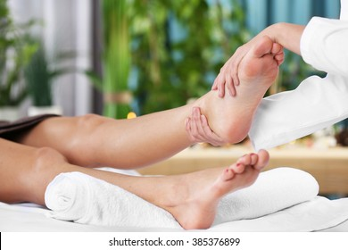 Beautiful young woman relaxing with leg massage at beauty spa