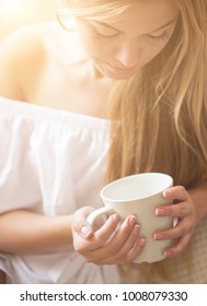 Beautiful young woman relaxing at living room while enjoying in coffee.