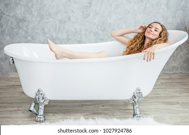 Beautiful young woman relaxing lying in the retro bathtube in the bathroom