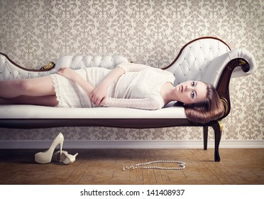 Beautiful young woman relaxing on a vintage sofa