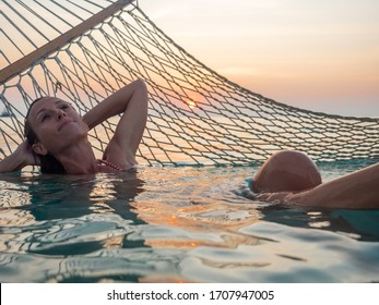 Beautiful young woman relaxing on hammock over sea at sunset enjoying peaceful vacations in dreamlike destination. Maldive Islands