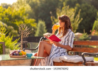 Beautiful young woman relaxing on a sunny summer morning in her backyard, having breakfast, drinking orange juice and reading a book outdoors