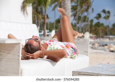 Beautiful young woman relaxing on luxury couch at the beach. Girl is wearing beautiful summer dress. Female with hands behind head is relaxing on lounge chair.