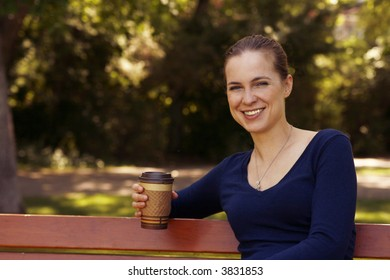 Beautiful young woman relaxing on park bench with a cup of coffee or tea.