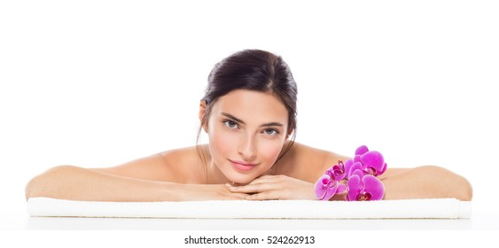 Beautiful young woman relaxing on towel with purple orchid flower isolated on white background. Portrait of girl enjoying massage. Banner of brunette girl lying down on front and looking at camera.