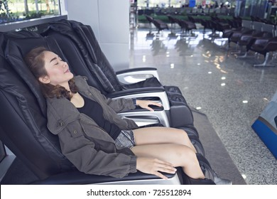 Beautiful young woman relaxing on the massage chair in airport.