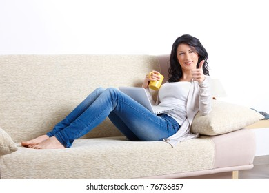 Beautiful young woman relaxing on sofa with laptop and a cup of tea showing thumb up in home