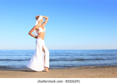 Beautiful young woman relaxing on the beach in Greece at sunset