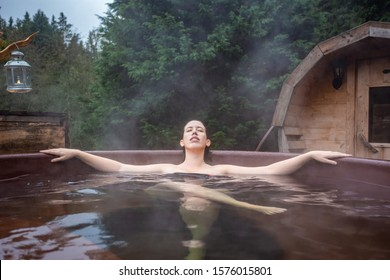 beautiful young woman relaxing in an outdoor hot tub on the forest. Otzarreta, Basque Country, Spain