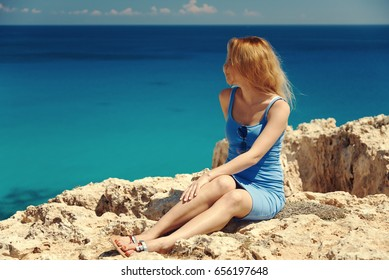 Beautiful young woman is relaxing sitting on the beautiful rocky coast.