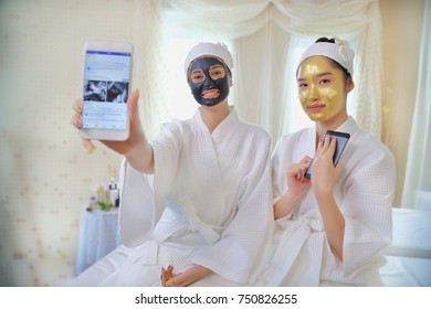Beautiful young woman relaxing with smartphone and face mask at beauty spa
