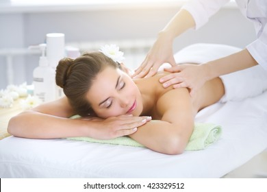 Beautiful young woman relaxing in the spa salon on light background