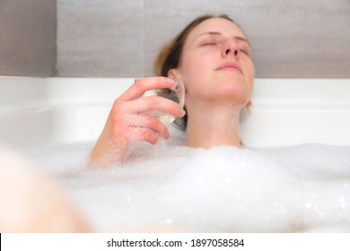 Beautiful young woman relaxing in a warm bubbly bath at home, enjoying a glass of white wine. Concept about lifestyle, relaxation and people.